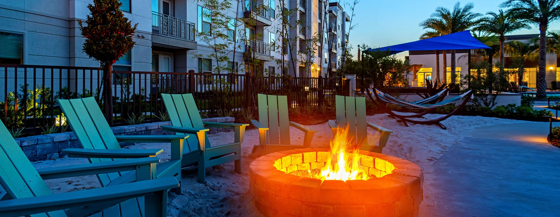 fire pit with lounge chairs at dusk